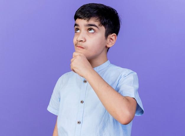 Przemyślany młody chłopak dotykając brody patrząc w górę na białym tle na fioletowej ścianie