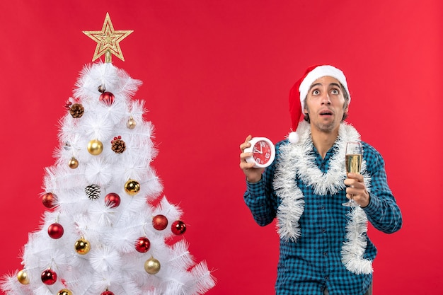 Przemyślany młody chłopak w kapeluszu świętego mikołaja i podnoszący kieliszek wina i trzymając zegar stojący w pobliżu choinki na czerwono