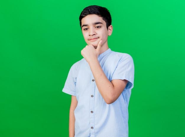 Przemyślany młody chłopiec kaukaski dotykając brody, patrząc w dół na białym tle na zielonej ścianie z miejsca na kopię