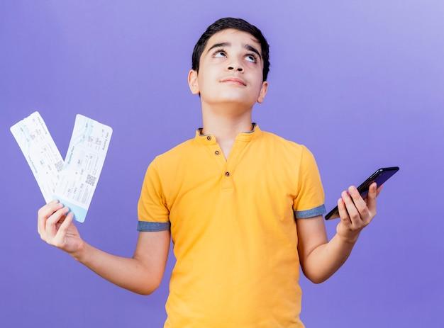 Przemyślany młody chłopiec kaukaski trzymając bilety lotnicze i telefon komórkowy patrząc na białym tle na fioletowym tle