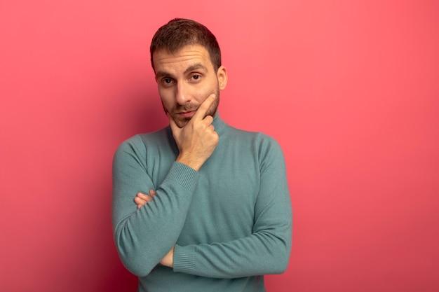 Przemyślany młody człowiek kaukaski, kładąc rękę na brodzie na białym tle na szkarłatnej ścianie z miejsca na kopię