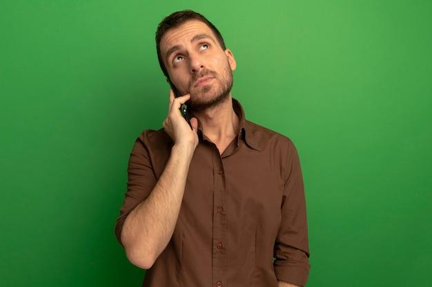 Przemyślany młody człowiek kaukaski rozmawia przez telefon patrząc na białym tle na zielonym tle z miejsca na kopię