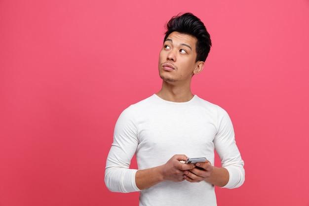 Przemyślany młody człowiek posiadający telefon komórkowy patrząc na rogu