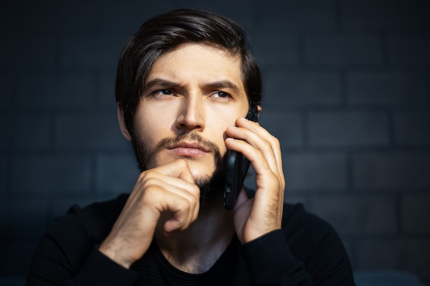 Przemyślany młody człowiek rozmawia smartphone na tle czarnego muru.