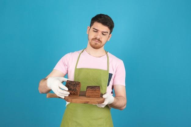 Przemyślany młody człowiek sprawdzanie plasterków ciasta.