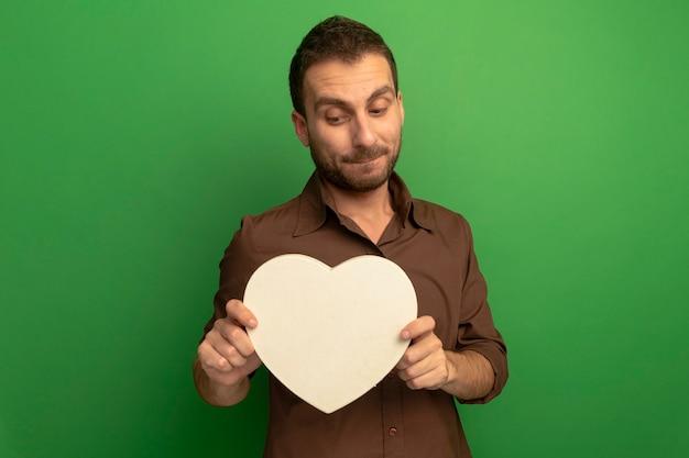 Przemyślany młody człowiek trzyma i patrząc na kształt serca na białym tle na zielonej ścianie