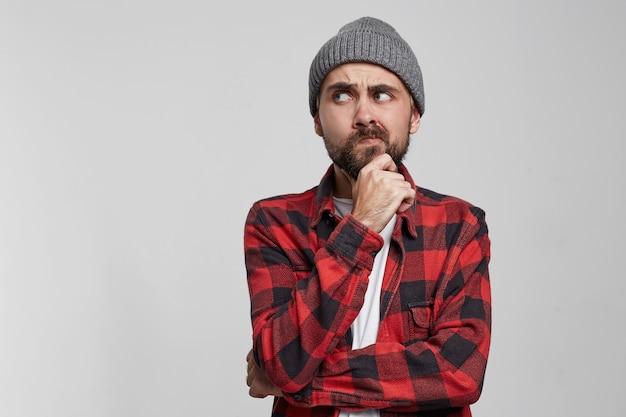 Przemyślany młody człowiek, trzymając rękę na brodzie i odwracając stojącego na białym tle nad białym