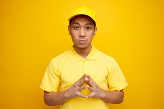 Przemyślany młody człowiek w czapce i mundurze, trzymając ręce razem