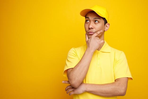 Przemyślany młody człowiek w czapce i mundurze, trzymając rękę na brodzie, patrząc w górę