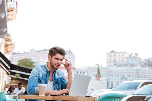 Przemyślany młody dorywczo mężczyzna patrzący na laptopa siedząc w kawiarni na świeżym powietrzu