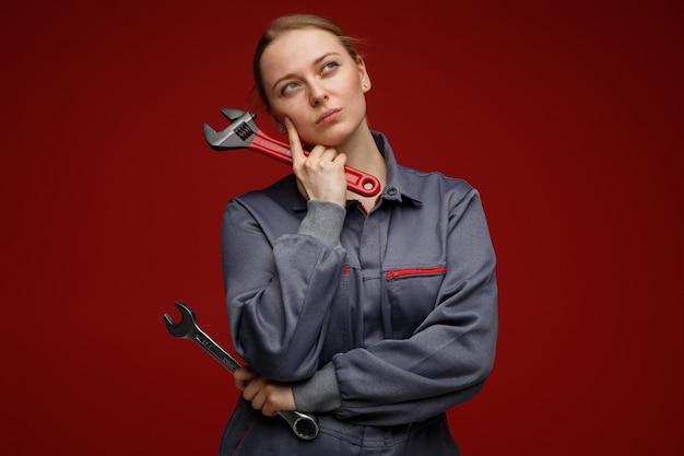 Przemyślany młody inżynier blond kobieta ubrana w mundur trzymając klucze trzymając palec na policzku patrząc w górę