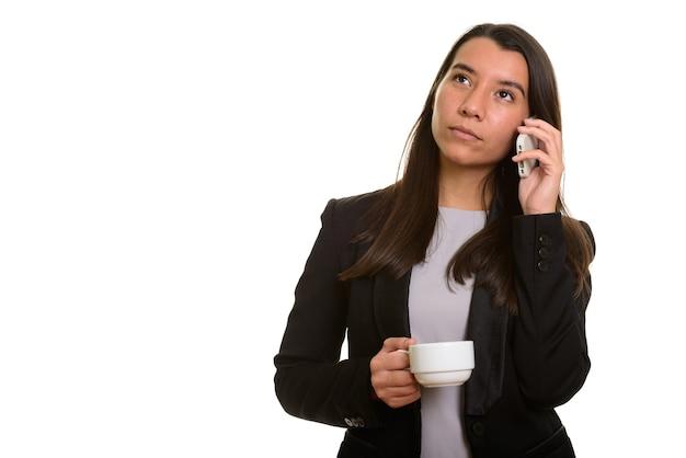 Przemyślany młody kaukaski bizneswoman rozmawia przez telefon komórkowy, trzymając filiżankę kawy