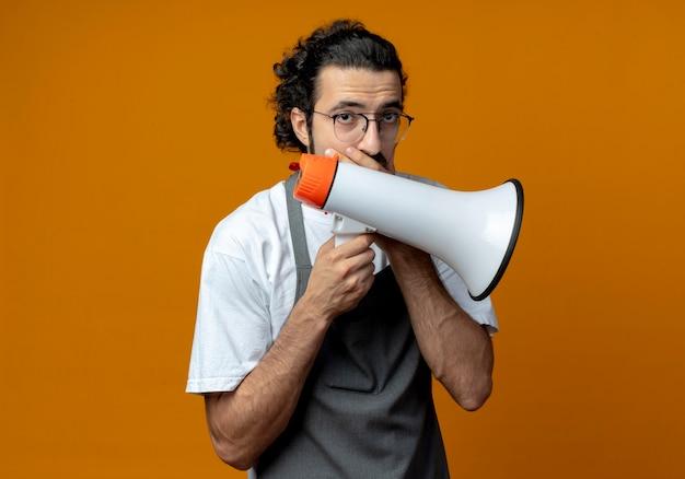 Przemyślany młody kaukaski fryzjer męski w mundurze i okularach, trzymając głośnik i kładąc rękę na ustach na białym tle na pomarańczowym tle z miejsca na kopię
