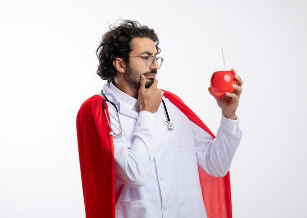 Przemyślany młody kaukaski mężczyzna w okularach optycznych w mundurze lekarza z czerwonym płaszczem i stetoskopem na szyi trzyma i patrzy na czerwony płyn chemiczny w szklanej kolbie