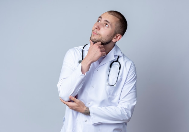 Przemyślany młody lekarz płci męskiej ubrany w szlafrok medyczny i stetoskop na szyi dotykający brody i łokcia patrząc w górę na białym tle na białej ścianie
