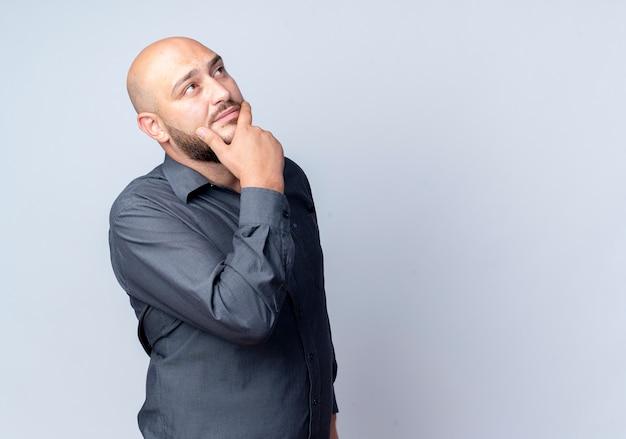 Przemyślany młody łysy mężczyzna call center dotykając brody i patrząc w górę na białym tle na białej ścianie