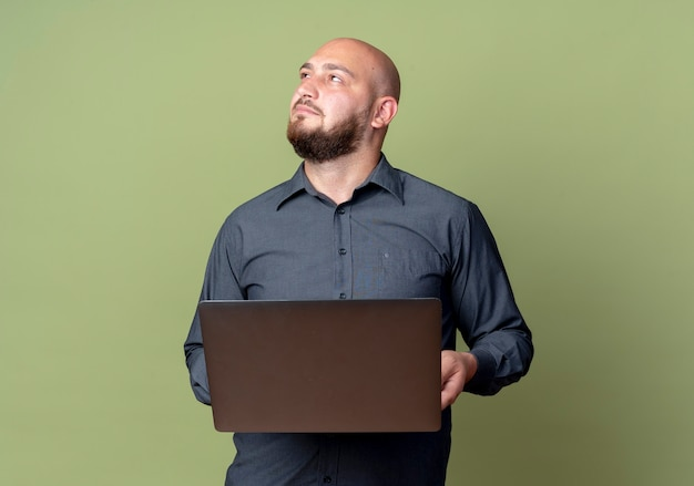 Przemyślany młody łysy mężczyzna call center gospodarstwa laptopa patrząc na białym tle na oliwkowej ścianie zielonej
