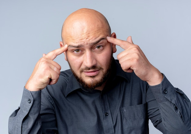 Przemyślany młody łysy mężczyzna call center kładzie palce na skroniach patrząc z przodu na białym tle na białej ścianie