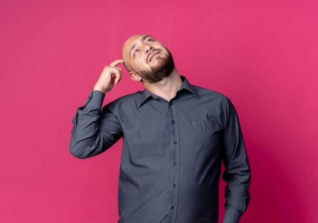 Przemyślany młody łysy mężczyzna call center patrząc w górę i kładąc palec na głowie na białym tle na szkarłatnej ścianie