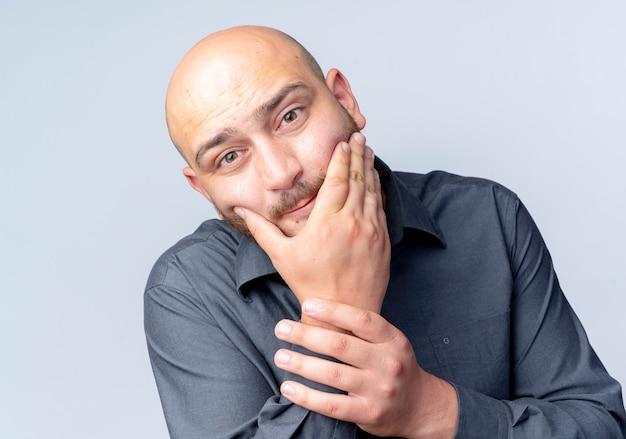 Przemyślany młody łysy mężczyzna call center patrząc z przodu kładąc rękę na brodzie i trzymając nadgarstek na białym tle na białej ścianie