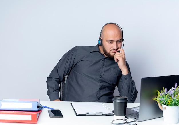 Przemyślany młody łysy mężczyzna call center sobie zestaw słuchawkowy siedzi przy biurku z narzędzi pracy patrząc na laptopa na białym tle na białej ścianie