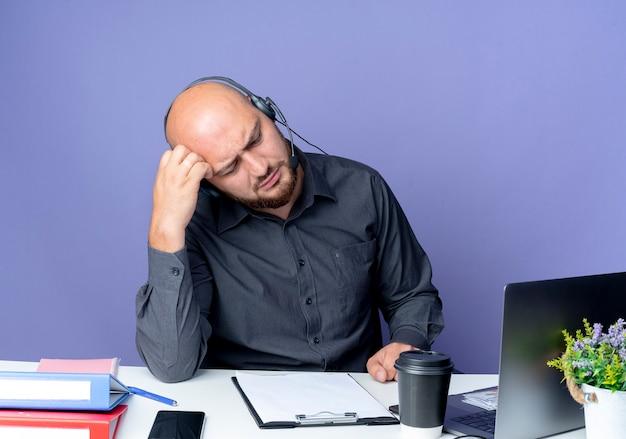 Przemyślany młody łysy mężczyzna call center sobie zestaw słuchawkowy siedzi przy biurku z narzędziami pracy kładąc rękę na głowie patrząc w dół na białym tle na fioletowej ścianie