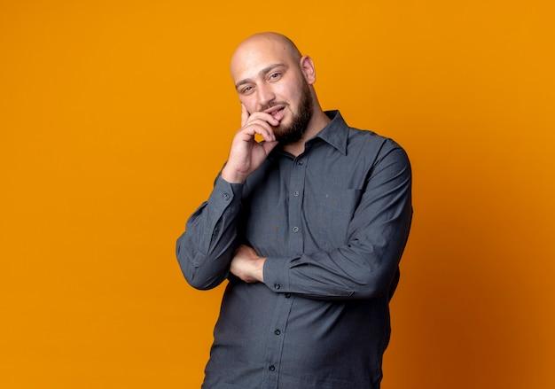 Przemyślany młody łysy mężczyzna call center stojący z zamkniętą postawą i kładąc rękę na brodzie na białym tle na pomarańczowej ścianie