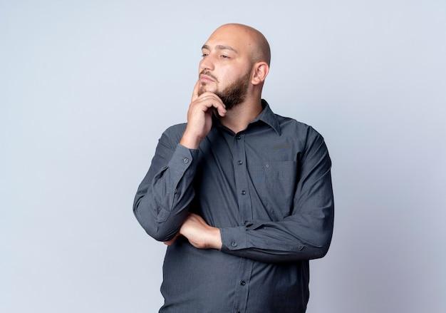 Przemyślany młody łysy mężczyzna call center stojący z zamkniętą postawą kładąc dłoń na brodzie, patrząc na bok na białym tle na białej ścianie