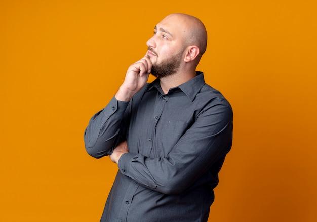 Przemyślany młody łysy mężczyzna call center stojący z zamkniętą postawą kładąc rękę na brodzie patrząc w górę na białym tle na pomarańczowej ścianie