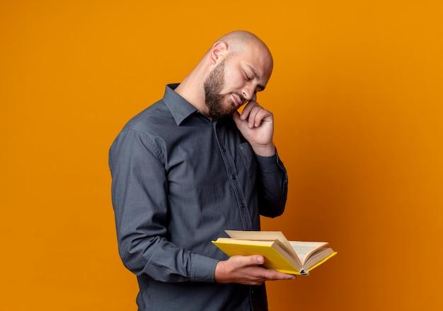 Przemyślany młody łysy mężczyzna call center trzyma książkę kładąc palec na świątyni z jednym okiem zamkniętym na białym tle na pomarańczowej ścianie