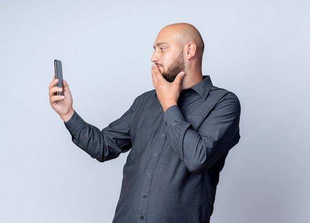 Przemyślany młody łysy mężczyzna call center trzymając i patrząc na telefon komórkowy z ręką na ustach na białym tle na białej ścianie