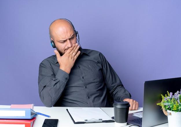 Przemyślany młody łysy mężczyzna z call center w zestawie słuchawkowym siedzący przy biurku z narzędziami roboczymi patrząc na laptopa z ręką na ustach odizolowany na fioletowej ścianie