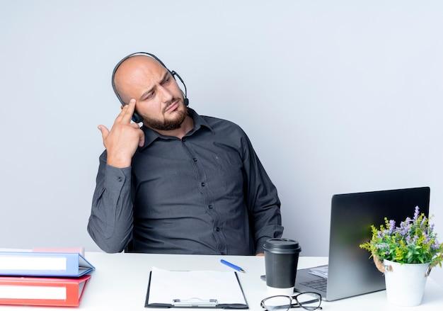 Przemyślany młody łysy mężczyzna z call center w zestawie słuchawkowym siedzący przy biurku z narzędziami roboczymi patrząc z boku i kładący palce na skroni odizolowanej na białej ścianie