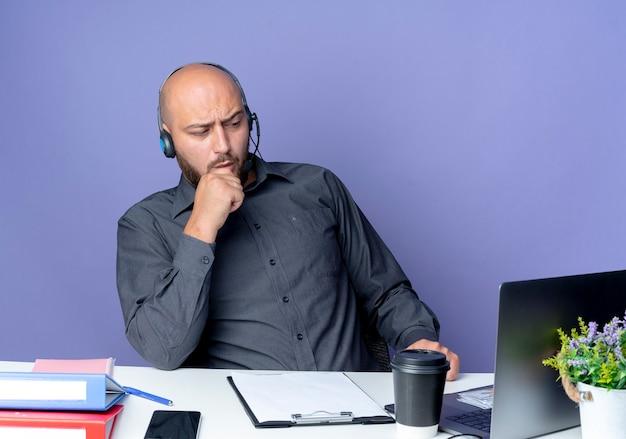 Przemyślany młody łysy mężczyzna z call center w zestawie słuchawkowym siedzący przy biurku z narzędziami roboczymi patrząc z przodu z ręką na brodzie odizolowany na fioletowej ścianie