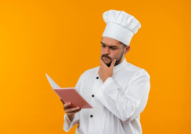 Przemyślany młody mężczyzna kucharz w mundurze szefa kuchni, trzymając i patrząc na notes z ręką na brodzie na białym tle na pomarańczowej przestrzeni