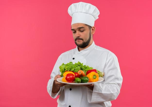 Przemyślany młody mężczyzna kucharz w mundurze szefa kuchni, trzymając i patrząc na talerz warzyw na białym tle na różowej przestrzeni