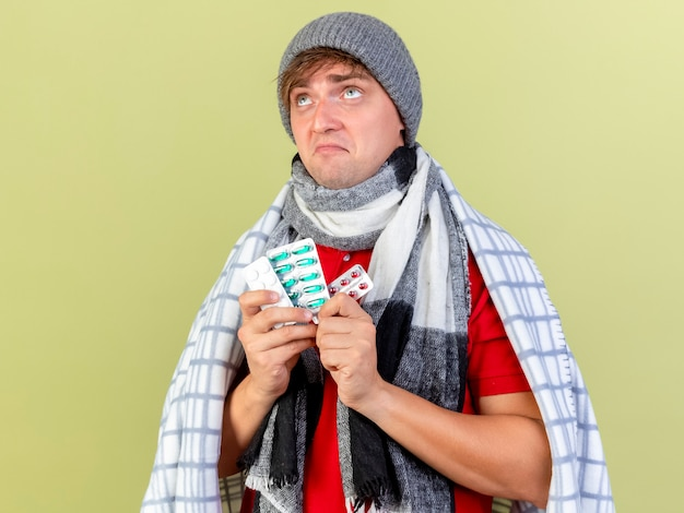 Przemyślany młody przystojny blondyn chory ubrany w czapkę zimową i szalik owinięty w kratę z paczkami tabletek medycznych patrząc w górę odizolowany na oliwkowej ścianie