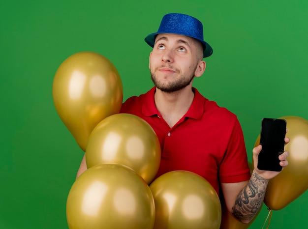 Przemyślany młody przystojny facet słowiańskich partii na sobie kapelusz partii stojącej wśród balonów pokazując telefon komórkowy patrząc na białym tle na zielonym tle