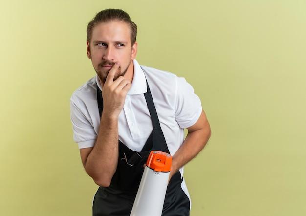 Przemyślany młody przystojny fryzjer trzymając rozmowę przez głośnik patrząc na bok, kładąc rękę na brodzie na białym tle na oliwkowej ścianie