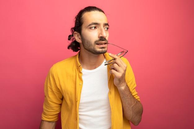 Przemyślany młody przystojny kaukaski mężczyzna dotyka wargi w okularach patrząc z boku na białym tle na szkarłatnej ścianie z miejsca na kopię