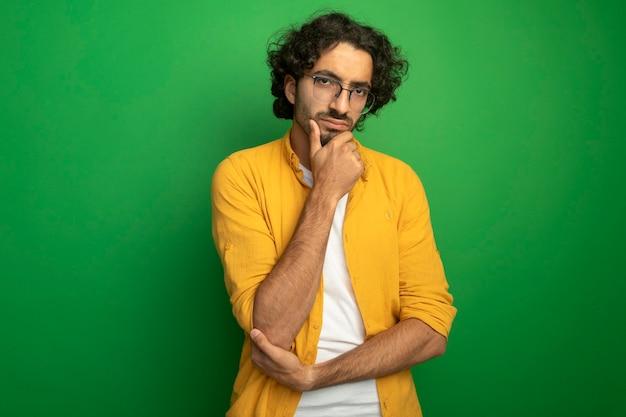Przemyślany młody przystojny kaukaski mężczyzna w okularach dotykając brody na białym tle na zielonej ścianie z miejsca na kopię