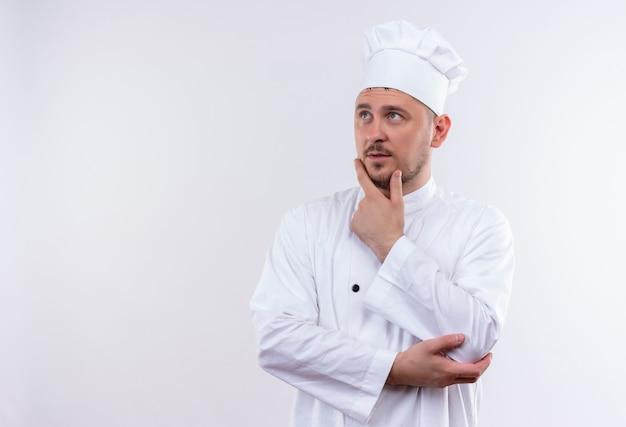 Przemyślany młody przystojny kucharz w mundurze szefa kuchni kładąc rękę na brodzie, patrząc na bok na białym tle na białej przestrzeni