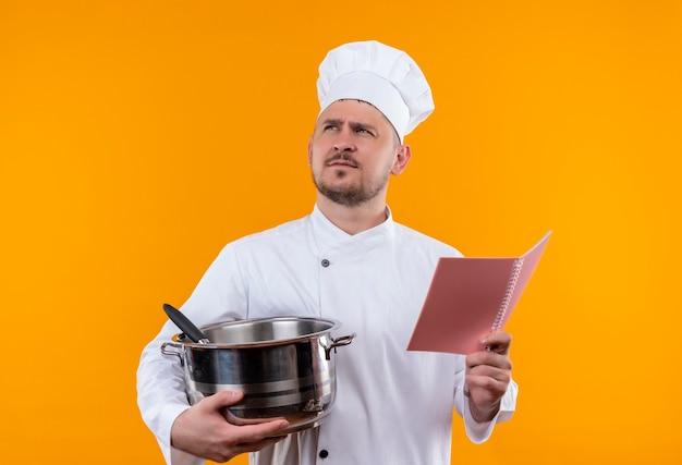 Przemyślany młody przystojny kucharz w mundurze szefa kuchni trzyma kocioł i notes patrząc na odizolowaną pomarańczową przestrzeń