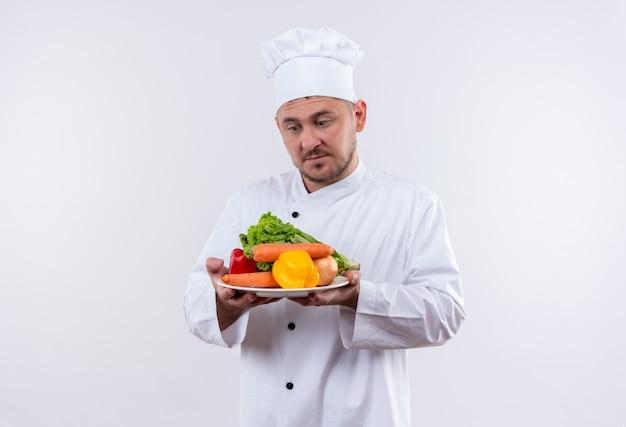 Przemyślany młody przystojny kucharz w mundurze szefa kuchni trzymając talerz z warzywami, patrząc na nich na na białym tle