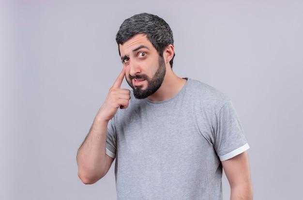 Przemyślany młody przystojny mężczyzna wyciągając dolną powiekę na białym tle na białej ścianie