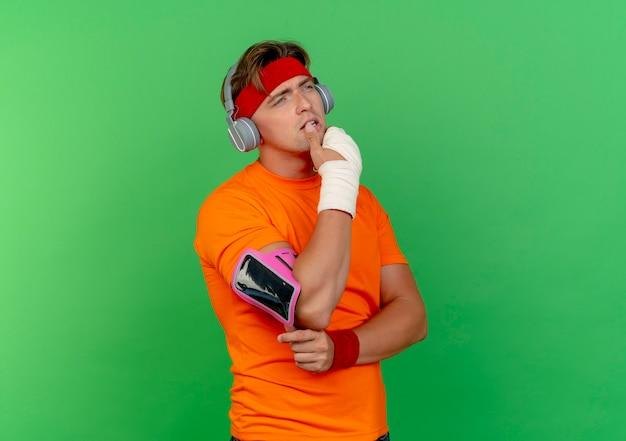 Przemyślany młody przystojny sportowy mężczyzna noszący opaskę na głowę i opaski oraz słuchawki i opaskę na telefon z nadgarstkiem owiniętym bandażem, kładąc palec na wardze patrząc prosto