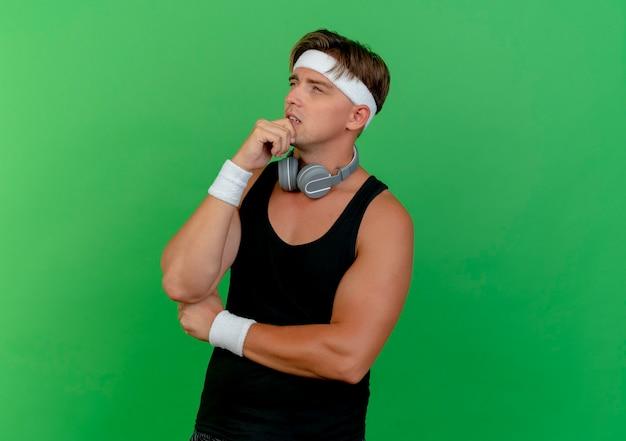Przemyślany młody przystojny sportowy mężczyzna ubrany w opaskę i opaski na rękę ze słuchawkami na szyi, patrząc z boku z ręką na brodzie odizolowaną na zielonej ścianie