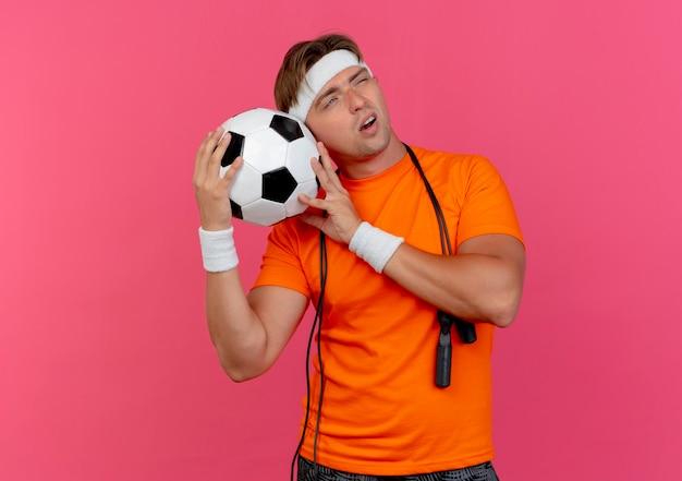 Przemyślany młody przystojny sportowy mężczyzna w opasce i opaskach na nadgarstek ze skakanką na szyi, trzymając piłkę nożną patrząc z boku odizolowaną na różowej ścianie