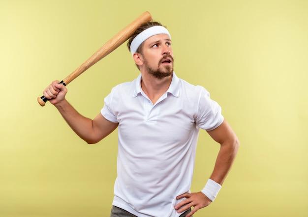 Przemyślany młody przystojny sportowy mężczyzna w opasce i opaskach na rękę trzymający kij bejsbolowy i kładący rękę na talii, patrząc z boku odizolowany na zielonej przestrzeni