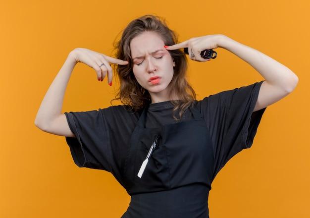 Przemyślany młody słowiański fryzjer żeński w mundurze trzymając maszynkę do strzyżenia włosów kładący palce na skroniach z zamkniętymi oczami na białym tle na pomarańczowym tle